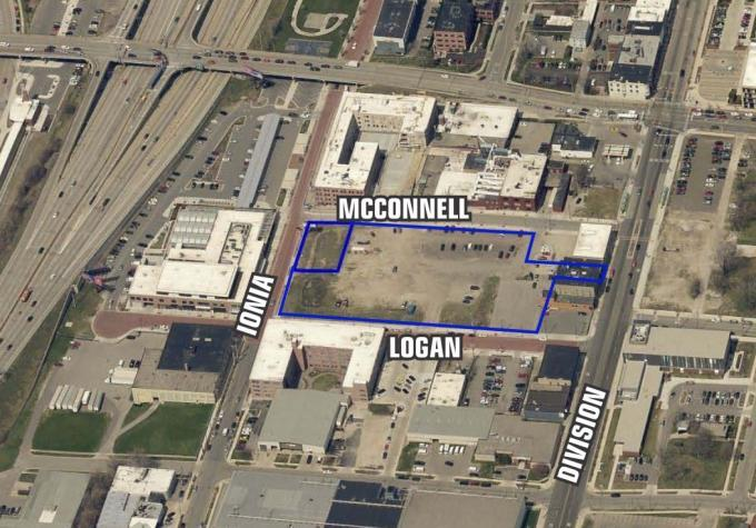 The city of Grand Rapids plans to build a 293-space parking lot across from the Downtown Market on land owned by an affiliate of Spectrum Industries.