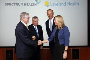 Lakeland Health and Spectrum Health finalized their merger agreement today. Pictured, from left, are Lakeland Health President and CEO Loren Hamel; Dan Hopp, chairman of the board of directors of Lakeland Health; Dick DeVos, chairman of the Spectrum Health System board of directors; and Spectrum Health President and CEO Tina Freese Decker.