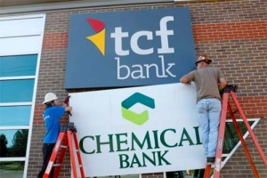 Universal Sign workers exchange Chemical Bank sign for TCF sign.