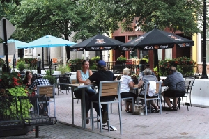 Diners in a designated social zone along Monroe Center in downtown Grand Rapids.